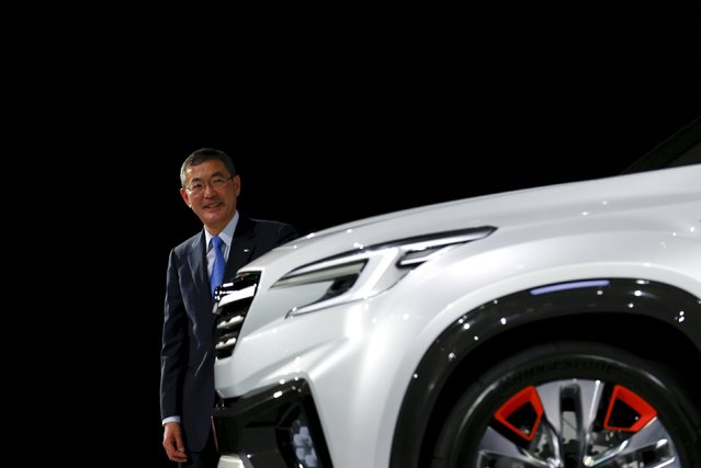 Yasuyuki Yoshinaga, president and chief executive officer of Fuji Heavy Industries Ltd, the maker of Subaru cars, poses next to a Subaru Viziv Future concept car at the 44th Tokyo Motor Show in Tokyo, Japan, October 28, 2015. (Photo by Thomas Peter/Reuters)
