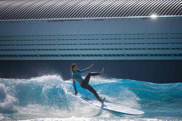 In a photo taken on October 18, 2020 a surfer falls on a wave at the Wave Park wave pool in Siheung, near Incheon. (Photo by Ed Jones/AFP Photo)