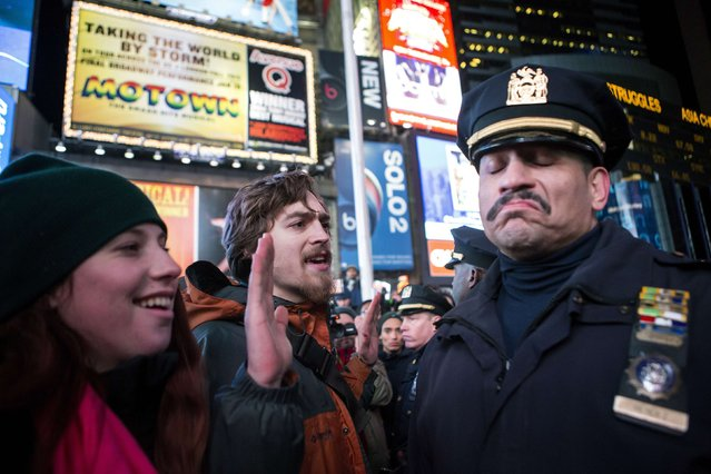 A NYPD policeman (R) reacts next to people protesting against the Staten Island death of Eric Garner during an arrest in July, at midtown Manhattan in New York December 3, 2014. (Photo by Eric Thayer/Reuters)