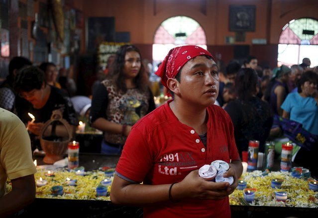 A man holds candles in a church in honor of San Simon in Chimaltenango, around 62 km (39 miles), from Guatemala City, October 28, 2015. (Photo by Jorge Dan Lopez/Reuters)