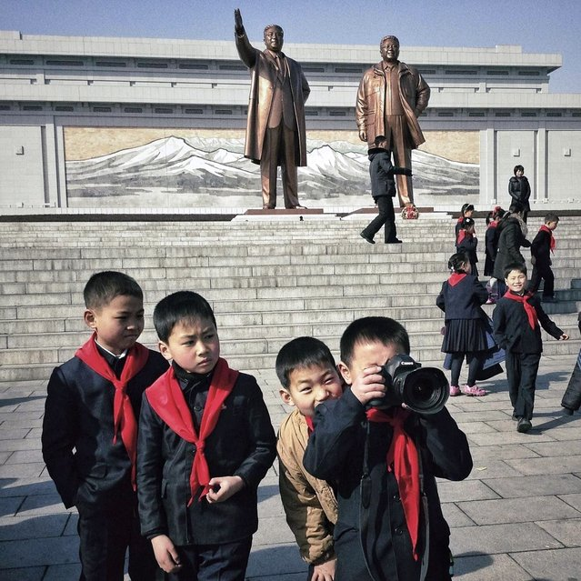 In this February 16, 2013 photo taken with an iPhone and posted to Instagram on February 16 , 2013, North Korean school boys play with an Associated Press photographer's professional camera in front of statues of the late leaders Kim Il Sung and Kim Jong Il, on Mansu Hill in Pyongyang, North Korea. (Photo by David Guttenfelder/AP Photo)
