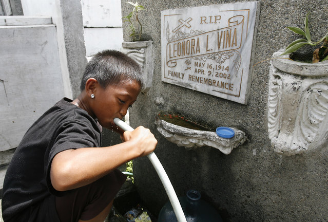 A boy drinks water from a hose atop a gravestone inside a cemetery in Manila, October 21, 2008. (Photo by Cheryl Ravelo/Reuters)