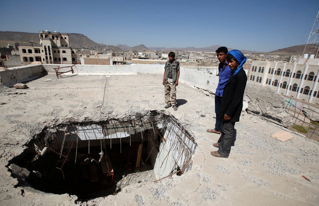 Boys stand by a hole caused by a Saudi-led air strike on the roof of their school last year, as schools open this week in Sanaa, the capital of war-torn Yemen October 5, 2016. (Photo by Khaled Abdullah/Reuters)