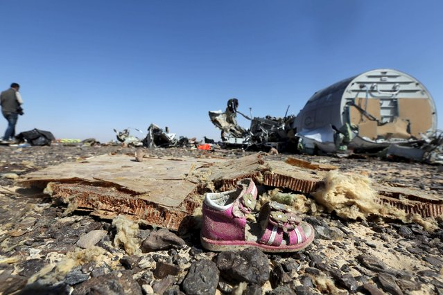 A child's shoe is seen in front of debris from a Russian airliner which crashed at the Hassana area in Arish city, north Egypt, November 1, 2015. (Photo by Mohamed Abd El Ghany/Reuters)