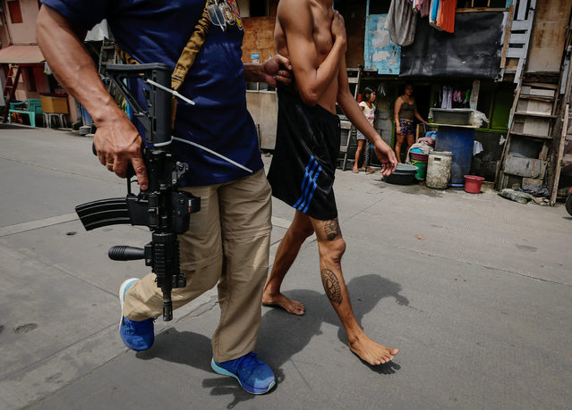 An alleged drug user is arrested during a police operation against illegal drugs at a slum area in Manila, Philippines, 06 October 2016. According to reports, three people were killed by the police during the operation, a couple of days after Philippine President Rodrigo Duterte lashed out in response to EU and US criticism of the anti-drug campaign launched by his government. Since Duterte took office on June 30, more than 3,500 people have been killed in military operations and extrajudicial executions carried out as part of the anti-drug campaign, according to reports. (Photo by Mark R. Cristino/EPA)