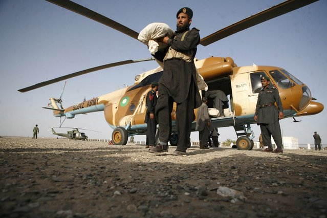 A paramilitary soldier carries a tent for survivors of an earthquake after unloading it from a helicopter in the town of Mashkeel, southwestern Pakistani province of Baluchistan, near the Iranian border April 18, 2013. The powerful earthquake struck a border area of southeast Iran on Tuesday killing at least 35 people in neighbouring Pakistan, destroying hundreds of houses and shaking buildings as far away as India and Gulf Arab states. (Photo by Naseer Ahmed/Reuters)
