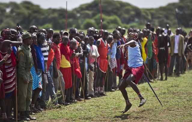 A young Maasai warrior throws a javelin at the annual Maasai Olympics in the Sidai Oleng Wildlife Sanctuary near to Mt Kilimanjaro, in southern Kenya Saturday, December 13, 2014. (Photo by Ben Curtis/AP Photo)