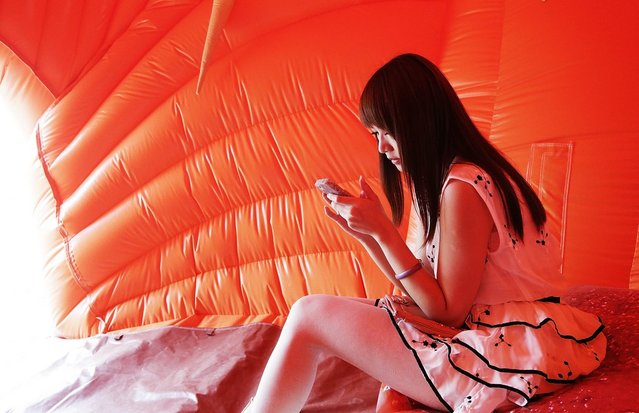 "A woman sits inside an inflatable sculpture of a pig called ""'House of Treasures"" by Chinese contemporary artist Cao Fei on display as part of the ""Inflation!"" exhibition curated by Mobile M + on April 24, 2013 in Hong Kong. The inflatable artwork is one of six on display as part of the exhibition which is open from April 25, 2013 until June 9, 2013. (Photo by Jessica Hromas)"