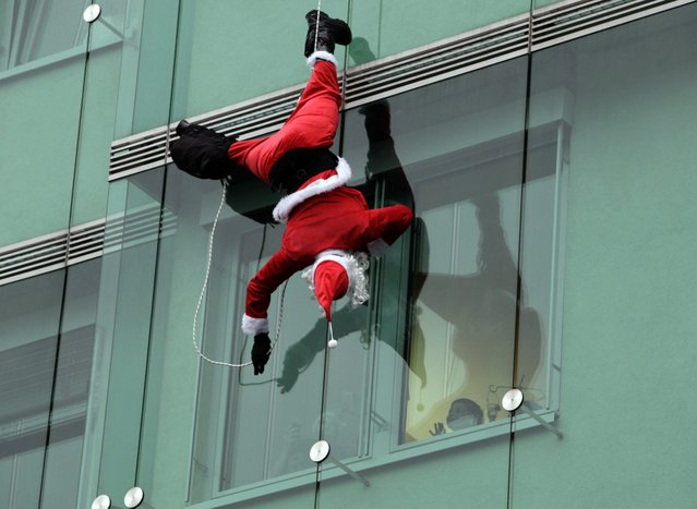 A member of the police special forces dressed in a Santa Claus suit waves to a patient as he abseils from the roof of a paediatric clinic in Ljubljana December 16, 2014. (Photo by Srdjan Zivulovic/Reuters)