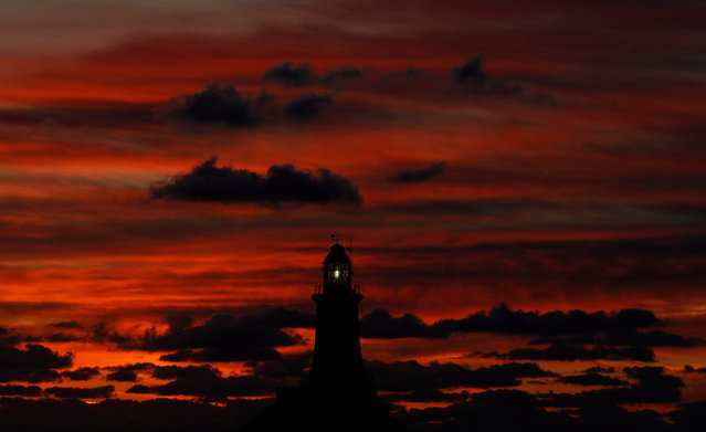 The sun sets behind La Corbiere lighthouse in Jersey, Britain November 8, 2017. (Photo by Darren Staples/Reuters)