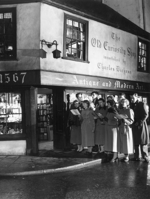 Students of King's College singing Christmas carols outside the Old Curiosity Shop, as immortalised by Charles Dickens, in Portsmouth Street, London, 12th December 1956. (Photo by Topical Press Agency/Getty Images)