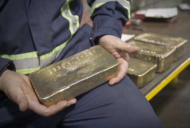 The worker holds the polished gold ingot. March 14, 2013; Tien Shan mountains, Kyrgyzstan. (Photo by Shamil Zhumatov/Reuters)