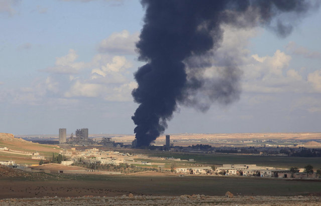 Smoke rises after what forces loyal to Syria's President Bashar al-Assad said were warehouses for rebel fighters in al-Maslamiyeh village burned as seen from al-Mallah Farms after Syria's army regained control of the area in north of Aleppo, December 15, 2014. (Photo by George Ourfalian/Reuters)