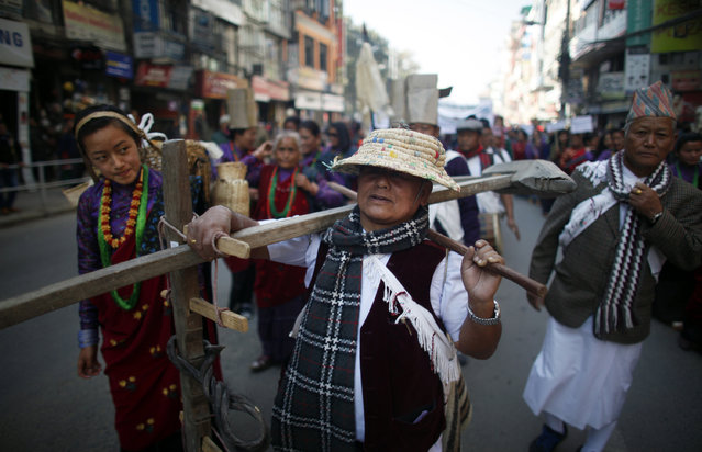 "A Nepalese Gurung community man carries a plough and participates in a parade to mark their New Year know as ""Tamu Loshar"" in Katmandu, Nepal, Tuesday, December 30, 2014. (Photo by Niranjan Shrestha/AP Photo)"