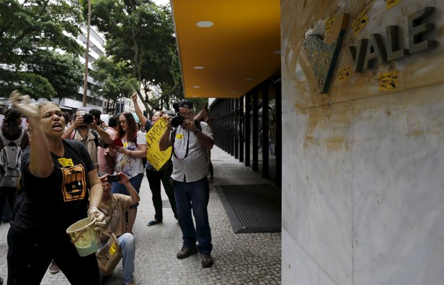 An environmental activist throws mud at a logo of Brazilian mining company Vale SA in front of the headquarters of the company in downtown Rio de Janeiro, Brazil, November 16, 2015. (Photo by Sergio Moraes/Reuters)