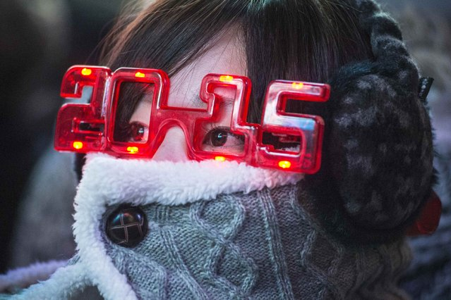 A woman wears 2015 glasses while taking cover from the cold weather during New Year's Eve celebrations in Times Square, New York December 31, 2014. (Photo by Stephanie Keith/Reuters)