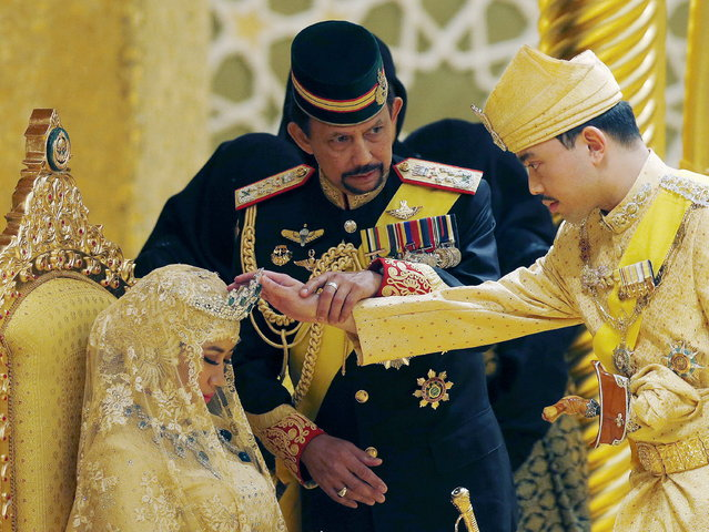 "Brunei's Sultan Hassanal Bolkiah holds the arm of his son Prince Abdul Malik to bless Malik's new wife Dayangku Raabi'atul 'Adawiyyah Pengiran Haji Bolkiah during the ""bersanding"" or enthronement ceremony at their wedding in the Nurul Iman Palace in Bandar Seri Begawan, April 12, 2015. (Photo by Olivia Harris/Reuters)"