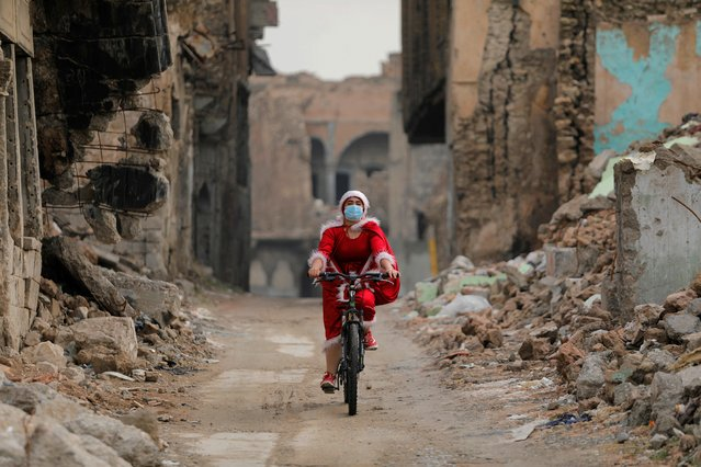 An Iraqi woman, dressed as Santa Claus, rides her bicycle amid the spread of the coronavirus in the old city of Mosul, Iraq, December 18, 2020. (Photo by Abdullah Rashid/Reuters)