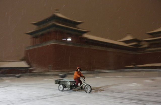 A man rides a tricycle cart past Wumen Gate of the Forbidden City as snow falls, at night in central Beijing, China, November 22, 2015. (Photo by Jason Lee/Reuters)