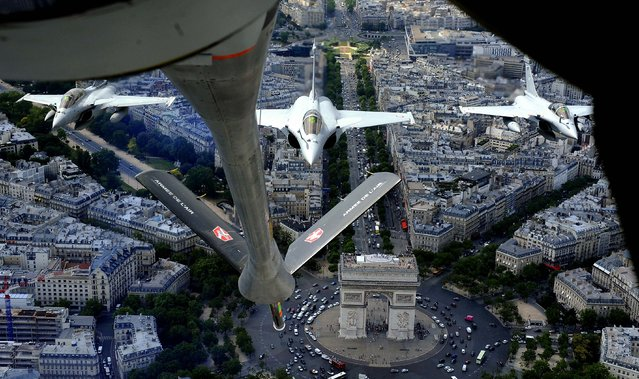 Seen from a refuelling plane, French Rafale jet fighters fly above the Arc of Triumph on a training mission over Paris, in preparation for the Bastille Day military parade. (Photo by Boris Horvat/AFP/Getty Images)