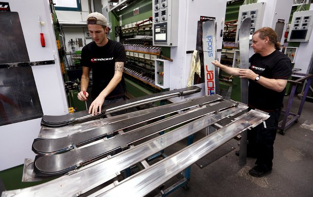 An employee fixes the layers of a ski in metallic molds before pressing it together at the plant of Swiss ski manufacturer Stoeckli in Malters, Switzerland November 25, 2015. (Photo by Arnd Wiegmann/Reuters)