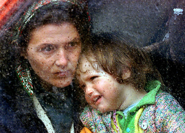 An ethnic Albanian refugee child crys on the shoulder of her mother as she takes shelter against the rain in a small camp, outside Kukes, a northern Albanian border town, 13 April 1999. The refugee family arrived two days ago in Albania after fleeing the town of Kosovo Polje in Yugoslavia. (Photo by Anja Niedringhaus/AFP Photo)