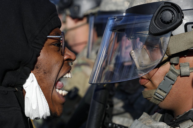 Protesters and National Guardsmen face off on East Lake Street, Friday, May 29, 2020, in St. Paul, Minn.  The massive protests sweeping across U.S. cities following the police killing of a black man in Minnesota have elevated fears of a new surge in cases of the coronavirus. Images showing thousands of screaming, unmasked protesters have sent shudders through the health community, who worry their calls for social distancing during the demonstrations are unlikely to be heard. (Photo by John Minchillo/AP Photo)