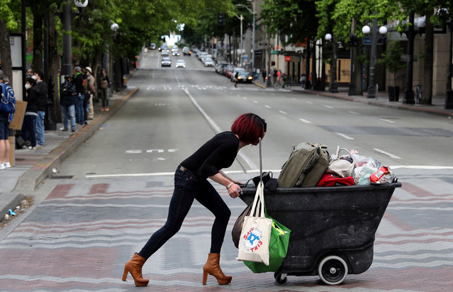 A woman pushes a cart during a protest against racial inequality and call for defunding of Seattle police, in Seattle downtown, Washington, U.S. June 14, 2020. (Photo by Goran Tomasevic/Reuters)