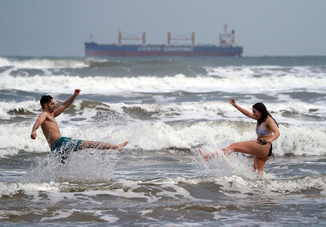 Ollie King, 22, and his sister Laura, 19, take a dip into the sea at King Edward's Bay in Tynemouth, United Kingdom on January 1, 2021. (Photo by Owen Humphreys/PA Images via Getty Images)