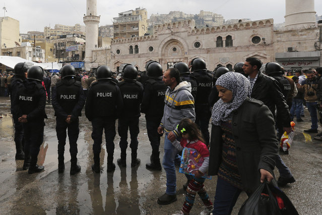 People walk past Jordanian police as they stand guard before a protest against satirical French weekly newspaper Charlie Hebdo, after the Friday prayer in Amman January 16, 2015. (Photo by Muhammad Hamed/Reuters)
