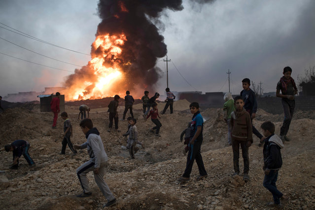 Children play next to a burning oil field in Qayara, south of Mosul, Iraq, Thursday, November 3, 2016. A senior military commander says more than 5,000 civilians have been evacuated from newly-retaken eastern parts of the Islamic State group-held city of Mosul and taken to camps. (Photo by Felipe Dana/AP Photo)