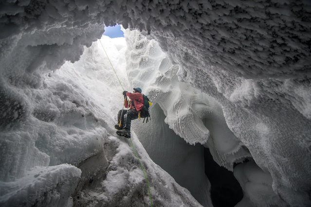 """Mount Erebus Ice Cave"". A scientist climbs out of an ice cave formed by volcanic vents near the summit of Mt. Erebus, Antarctica. (Photo and caption by Alasdair Turner/National Geographic Traveler Photo Contest)"