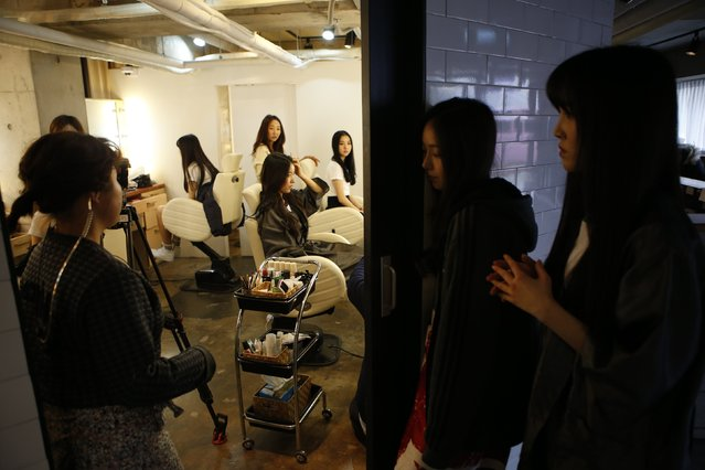 Members from South Korean girl group GFriend receive a makeover as SinB (R 2nd) and Yuju (R) look on at a beauty salon in Seoul December 23, 2014. (Photo by Kim Hong-Ji/Reuters)