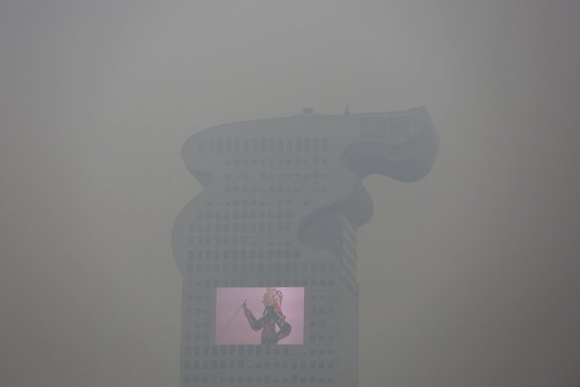 "A building and a large screen are seen through thick smog in Beijing December 8, 2015 as China's capital issues its first ever ""red alert"" for pollution. (Photo by Damir Sagolj/Reuters)"