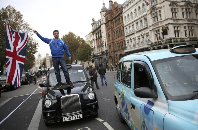 A protester waves a Union Jack flag as taxi drivers block Whitehall with their vehicles during a protest to call for an enquiry into Transport for London (TFL) in London, Britain November 8, 2016. (Photo by Neil Hall/Reuters)