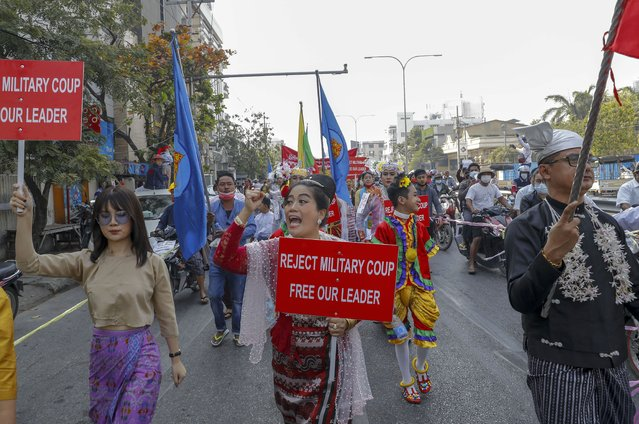 Demonstrators with Myanmar national flags shout slogans against the military coup during a protest march in Mandalay, Myanmar on Thursday, February 11, 2021. Large crowds demonstrating against the military takeover in Myanmar again defied a ban on protests Thursday, even after security forces ratcheted up the use of force against them and raided the headquarters of the political party of ousted leader Aung San Suu Kyi a day earlier. (Photo by AP Photo/Stringer)