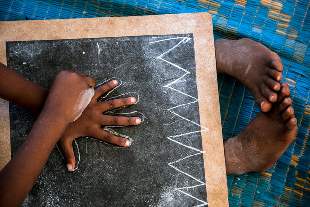 """First drawing"". A child in a nursery Zanzibar draws his hand on a blackboard. Location: Tanzania. (Photo and caption by Beniamino Pisati/National Geographic Traveler Photo Contest)"