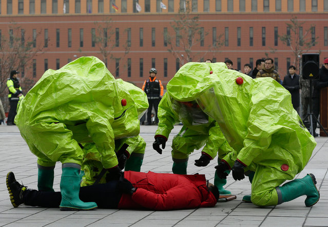 South Korean firefighters wearing protective gear take care of  a mock victim during an exercise against a possible terrorist attack in Seoul, South Korea, Thursday, January 29, 2015. The Seoul Metropolitan Police Agency said that the exercise is a part of preparation to prepare the city since threats of terrorism are growing worldwide. (Photo by Ahn Young-joon/AP Photo)