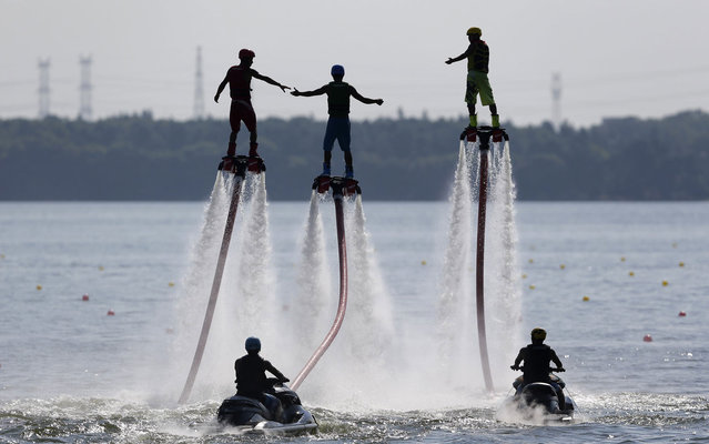People riding on water-powered jet-boards perform at Donghu lake in Wuhan in the Hubei province of China on July 25, 2013. (Photo by Darley Shen/Reuters)