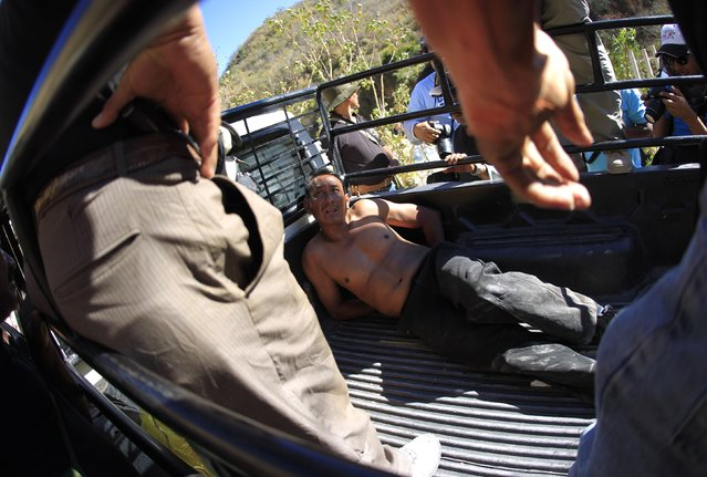 Members of the Community Police of the FUSDEG (United Front for the Security and Development of the State of Guerrero) stand at the back of a lorry with a man they captured after a shootout against a group, that villagers suspect of belonging to a local gang, at a hill in the village of Petaquillas, on the outskirts of Chilpancingo, in the Mexican state of Guerrero, February 1, 2015. (Photo by Jorge Dan Lopez/Reuters)