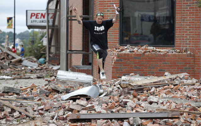 A local resident leaps over rubble from a tornado damaged building, Friday, July 20, 2018, in Marshalltown, Iowa. Several buildings were damaged Thursday evening by a tornado in the main business district in town including the historic courthouse. (Photo by Charlie Neibergall/AP Photo)