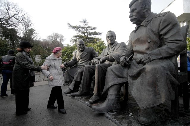 Women stand next to the sculptures of (R-L) Soviet dictator Josef Stalin, U.S. President Franklin Roosevelt and British Prime Minister Winston Churchill, made by Zurab Tsereteli, during its opening ceremony in the settlement of Livadia, Yalta region, Crimea, February 5, 2015. (Photo by Pavel Rebrov/Reuters)