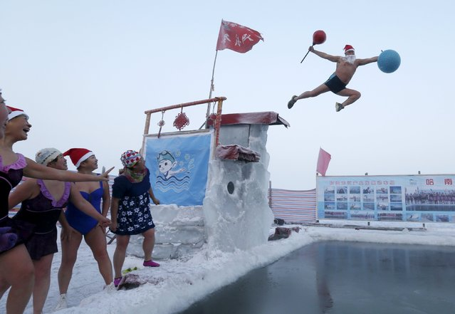 Winter swimmers (L) look on as a man (R) wearing a Santa Claus hat and beard jumps into a pool carved into thick ice covering the Songhua River, to celebrate the upcoming Christmas, in Harbin, Heilongjiang province, China, December 24, 2015. (Photo by Sheng Li/Reuters)