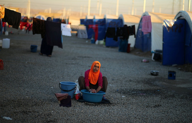 A displaced Iraqi woman, who fled the Islamic State stronghold of Mosul, washes clothes at Khazer camp, Iraq November 24, 2016. (Photo by Mohammed Salem/Reuters)