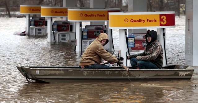 Paul Dusablon, left, and Richard Kotva row from the Circle K at Springdale Park after helping the owner move electronics off the floor inside the convenience store, in Fenton, Mo., Wednesday, December 30, 2015. A rare winter flood threatened nearly two dozen federal levees in Missouri and Illinois as rivers rose, prompting evacuations in several places. (Photo by Robert Cohen/St. Louis Post-Dispatch via AP Photo)