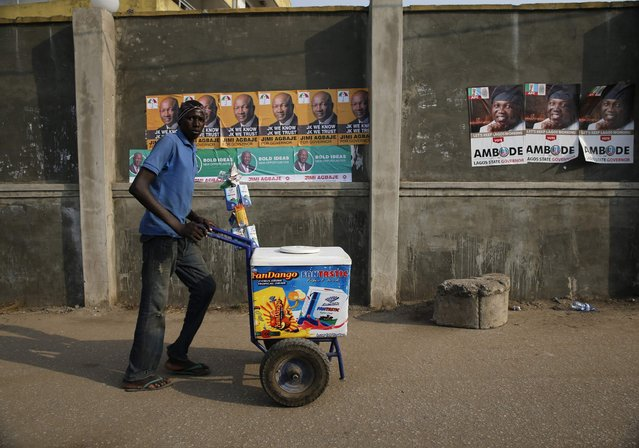 Garuba Musa, 27, an ethnic Hausa Muslim man, pushes an ice-cream cart in Ikeja district in Lagos January 26, 2015. Musa is from the north of Nigeria and hopes the forthcoming Presidential election will be peaceful but fears Boko Haram may hamper the process in the north of the country. (Photo by Akintunde Akinleye/Reuters)