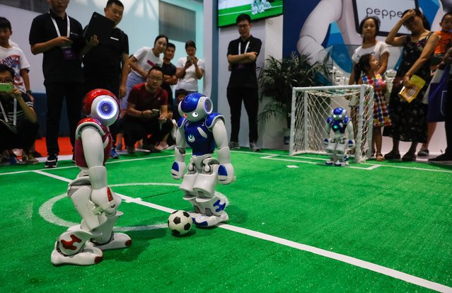 Visitors watch robots playing football during the 2018 World Robot conference in Beijing, China, 15 August 2018. The conference will be held from 15 to 19 August and will include a conference on robotics, an exhibition and a robot competition with the participation of robotics enterprises to showcase their robot products. (Photo by Roman Pilipey/EPA/EFE/Rex Features/Shutterstock)