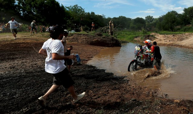 People run to help KTM motorcycle rider Laia Sanz of Spain during the Buenos Aires-Rosario prologue stage of Dakar Rally 2016 in Arrecifes, Argentina, January 2, 2016. (Photo by Marcos Brindicci/Reuters)