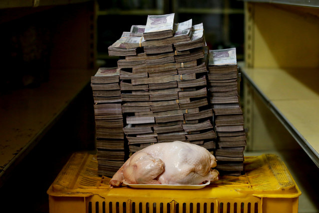 A 2.4 kg chicken is pictured next to 14,600,000 bolivars, its price and the equivalent of 2.22 USD, at a mini-market in Caracas, Venezuela August 16, 2018. It was the going price at an informal market in the low-income neighborhood of Catia. (Photo by Carlos Garcia Rawlins/Reuters)
