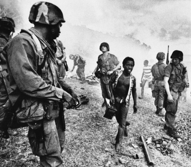 A young Grenadian boy carries an empty ammo box as he walks through members of the military police attached to the 82nd airborne in Marimount, Grenada on Thursday, December 9, 1983. The soldiers where taking part in a live fire exercise. (Photo by Paul R. Benoit/AP Photo)